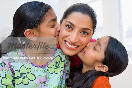 Portrait of daughters kissing mother on cheeks Stock Photo - Premium Royalty-Free, Image code: 604-01123428