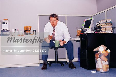Businessman at messy desk with coffee and doughnut/