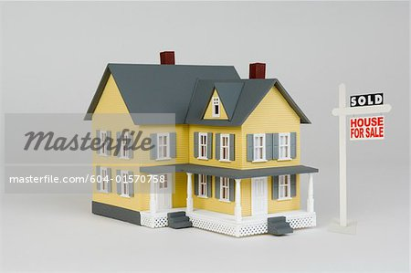 Miniature house and for sale sign Stock Photo - Premium Royalty-Free, Image code: 604-01570758