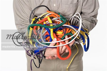 Man holding tangled power cords Stock Photo - Premium Royalty-Free, Image code: 604-01742081