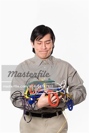 Man holding tangled power cords Stock Photo - Premium Royalty-Free, Image code: 604-01742112