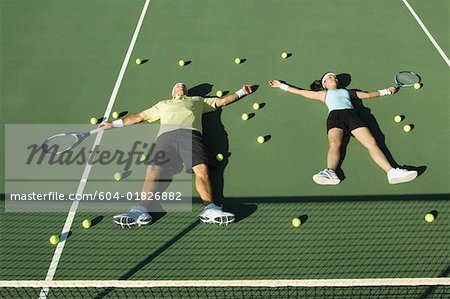 Tennis players lying down on tennis court Stock Photo - Premium Royalty-Free, Image code: 604-01826882