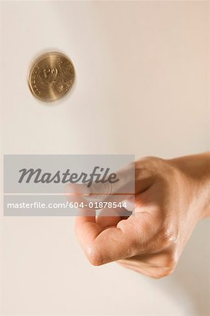 Hand flipping coin Stock Photo - Premium Royalty-Free, Image code: 604-01878544