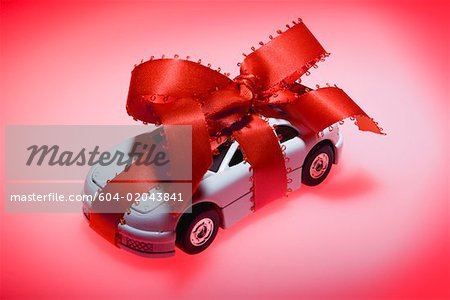 Toy car wrapped in ribbon Stock Photo - Premium Royalty-Free, Image code: 604-02043841