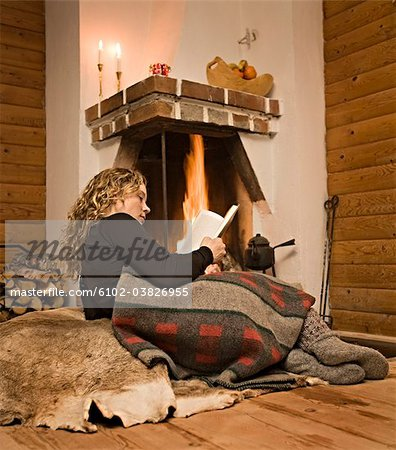 A woman reading a book in front of a fireplace, Sweden. Stock Photo - Premium Royalty-Free, Image code: 6102-03826955