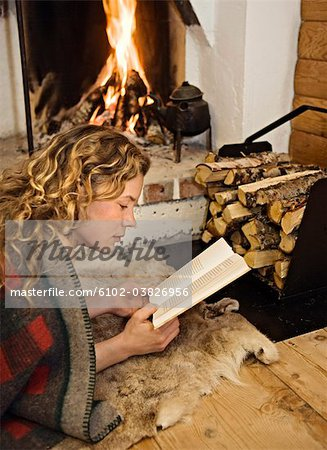 A woman reading infront of  a fireplace, Sweden. Stock Photo - Premium Royalty-Free, Image code: 6102-03826956