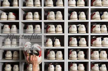 Hand picking shoes on shelves in a bowling alley. - Stock Photo ...