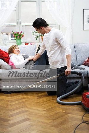 A pregnant woman lying on a couch and a man vacuuming, Sweden. Stock Photo - Premium Royalty-Free, Image code: 6102-03827878