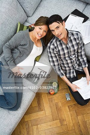 A pregnant woman and a man discussing their home finances, Sweden. Stock Photo - Premium Royalty-Free, Image code: 6102-03827907