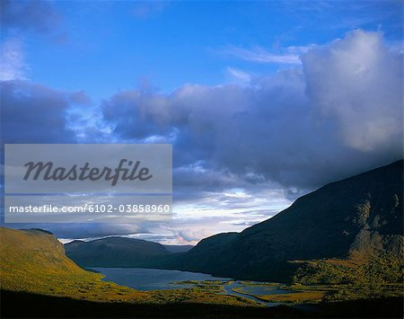 Lake surrounded by mountains Stock Photo - Premium Royalty-Free, Image code: 6102-03858960