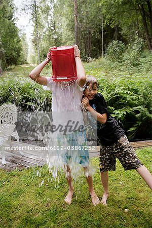 Boys playing with water in a garden a summer day, Sweden. Stock Photo - Premium Royalty-Free, Image code: 6102-03867252