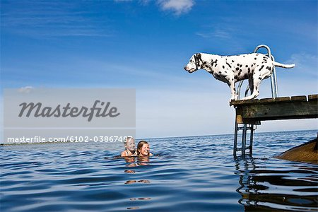 Dog on a jetty and girls swimming, Oland, Sweden. Stock Photo - Premium Royalty-Free, Image code: 6102-03867487