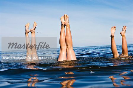Three pair of legs in the water, Sweden. Stock Photo - Premium Royalty-Free, Image code: 6102-03867489