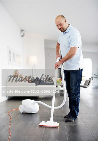 A man vacuuming a floor, Sweden. Stock Photo - Premium Royalty-Free, Image code: 6102-03904106