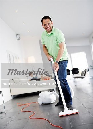 A man vacuuming a floor, Sweden. Stock Photo - Premium Royalty-Free, Image code: 6102-03904110