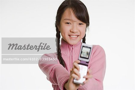 Happy girl using a mobile phone. Stock Photo - Premium Royalty-Free, Image code: 6102-03905450