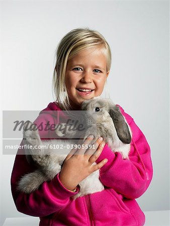 Portrait of a girl with a rabbit in her arms. Stock Photo - Premium Royalty-Free, Image code: 6102-03905591