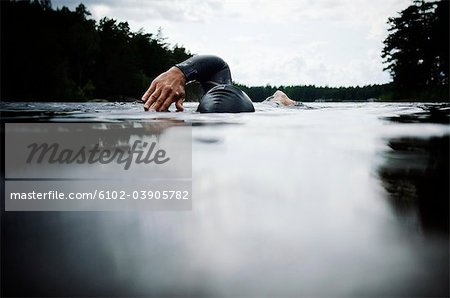 Woman swimming in water Stock Photo - Premium Royalty-Free, Image code: 6102-03905782
