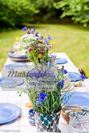 Flower vase and plates arranged on dining table Stock Photo - Premium Royalty-Free, Image code: 6102-03905791