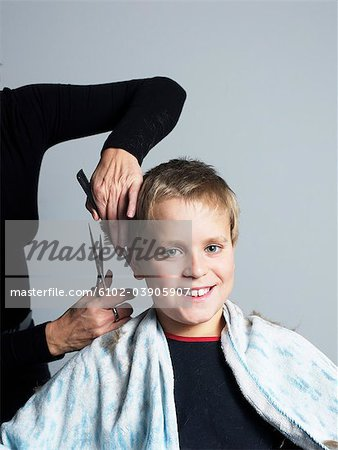 Boy getting haircut Stock Photo - Premium Royalty-Free, Image code: 6102-03905907
