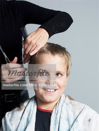 Woman cutting boys hair Stock Photo - Premium Royalty-Free, Image code: 6102-03905908