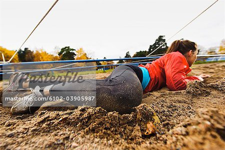 Woman crawling on ground Stock Photo - Premium Royalty-Free, Image code: 6102-03905987