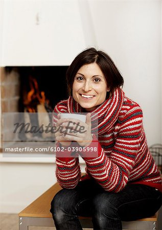 Woman drinking tea near fireplace Stock Photo - Premium Royalty-Free, Image code: 6102-03905998