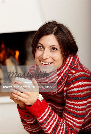 Woman drinking tea near fireplace Stock Photo - Premium Royalty-Free, Image code: 6102-03905999