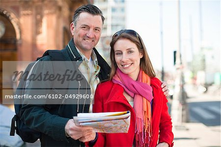 Portrait of couple with map sightseeing in city Stock Photo - Premium Royalty-Free, Image code: 6102-04929600