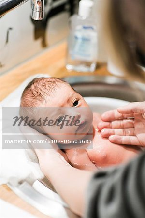 Mother bathing newborn baby Stock Photo - Premium Royalty-Free, Image code: 6102-05603683