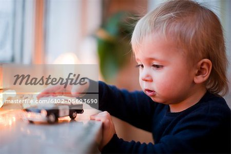 Boy playing with toy car Stock Photo - Premium Royalty-Free, Image code: 6102-05603690