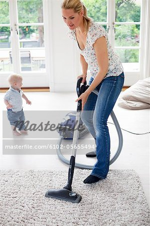 Mother vaccuming the livingroom Stock Photo - Premium Royalty-Free, Image code: 6102-05655494