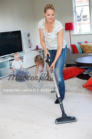 Mother vaccuming with her daughters playing in the background Stock Photo - Premium Royalty-Free, Image code: 6102-05655495