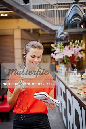 Young woman talking on mobile phone using earbud Stock Photo - Premium Royalty-Free, Image code: 6102-06025899