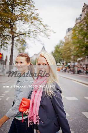Portrait of two women walking in street Stock Photo - Premium Royalty-Free, Image code: 6102-06025972