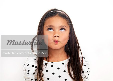 Portrait of girl making face, studio shot Stock Photo - Premium Royalty-Free, Image code: 6102-06336535
