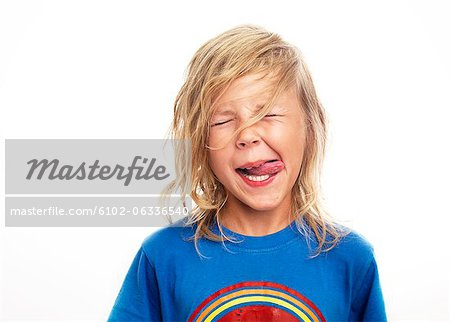 Portrait of boy sticking out tongue, studio shot Stock Photo - Premium Royalty-Free, Image code: 6102-06336540