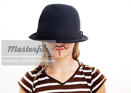 Portrait of girl wearing hat with fake moustache, studio shot Stock Photo - Premium Royalty-Free, Image code: 6102-06336546
