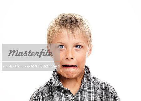 Portrait of boy making face, studio shot Stock Photo - Premium Royalty-Free, Image code: 6102-06336547