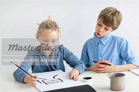 Boy and girl caligraphing chinese signs Stock Photo - Premium Royalty-Free, Image code: 6102-06336652