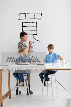 Boy, girl and female teacher caligraphing chinese signs Stock Photo - Premium Royalty-Free, Image code: 6102-06336654