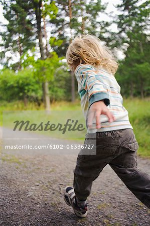 Child running through forest Stock Photo - Premium Royalty-Free, Image code: 6102-06336727