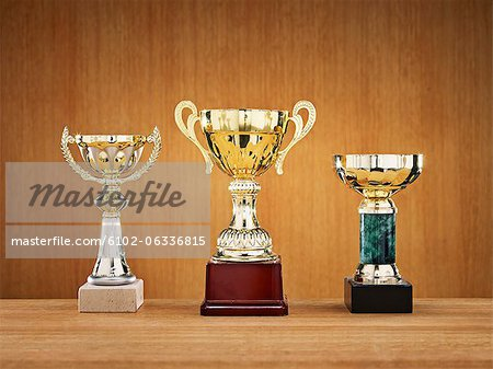 Trophies on wooden background Stock Photo - Premium Royalty-Free, Image code: 6102-06336815