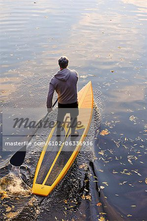 Man rowing paddle board in water, elevated view Stock Photo - Premium Royalty-Free, Image code: 6102-06336936
