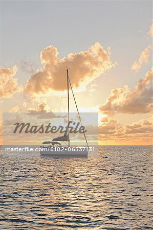 Sailing boat against sunset Stock Photo - Premium Royalty-Free, Image code: 6102-06337131