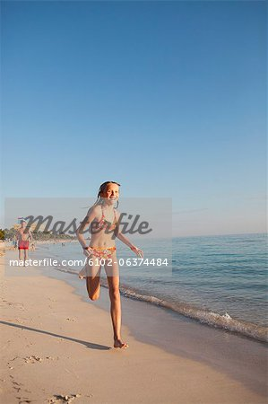 Girl running on beach Stock Photo - Premium Royalty-Free, Image code: 6102-06374484
