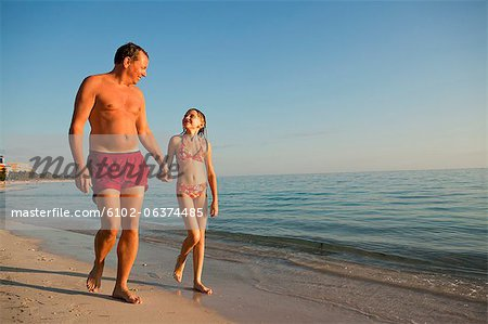 Father with daughter walking on beach Stock Photo - Premium Royalty-Free, Image code: 6102-06374485