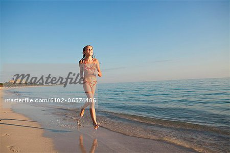 Girl running on beach Stock Photo - Premium Royalty-Free, Image code: 6102-06374486