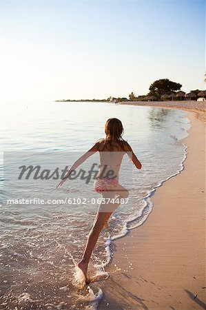 Girl running on beach Stock Photo - Premium Royalty-Free, Image code: 6102-06374487