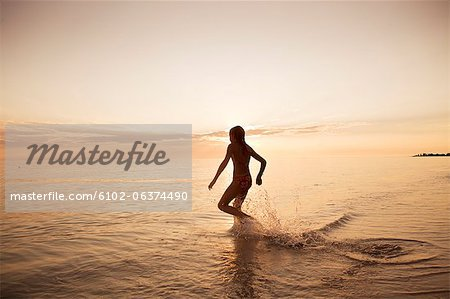Silhouette of girl running into sea Stock Photo - Premium Royalty-Free, Image code: 6102-06374490